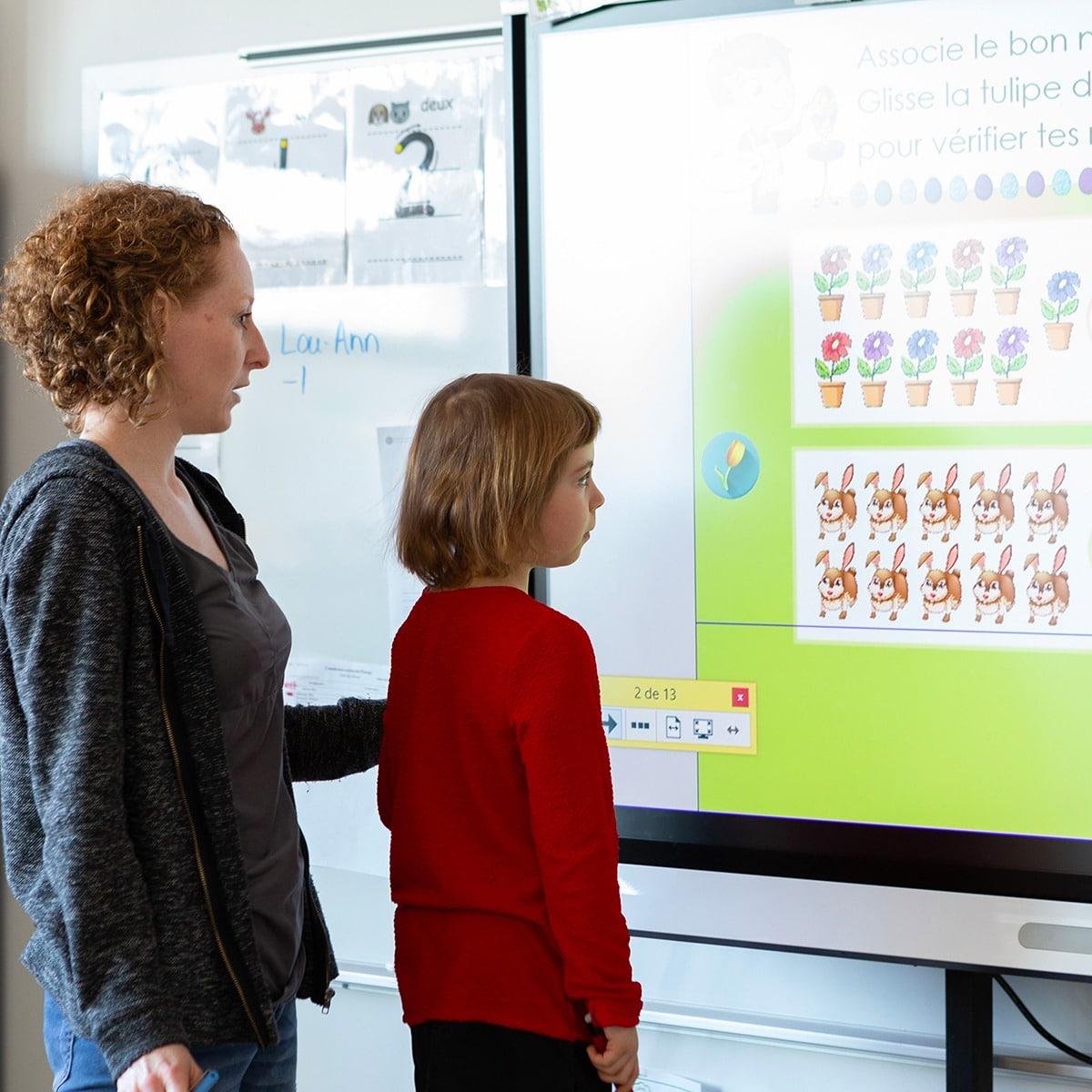 Photo d'une enseignante et d'une élève devant un tableau
